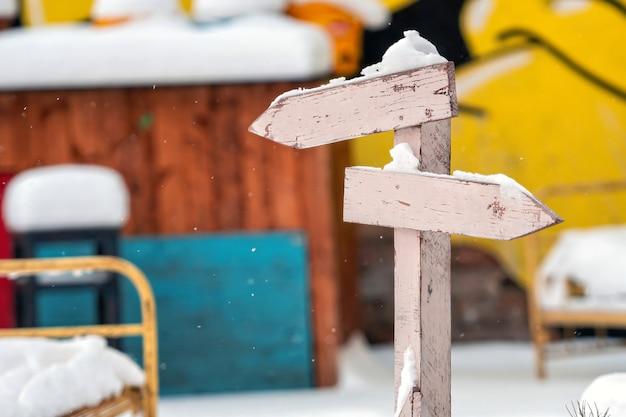 Zaśnieżony drewniany drogowskaz z dwiema pustymi strzałkami na kolorowej rozmytej powierzchni