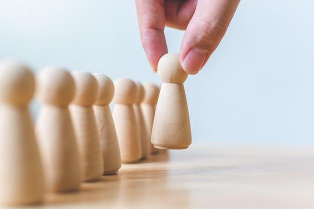 Zasoby ludzkie, zarządzanie talentami, rekrutacja pracowników, koncepcja lidera zespołu odnoszącego sukcesy w biznesie. ręka wybiera drewnianych ludzi wyróżniających się z tłumu.