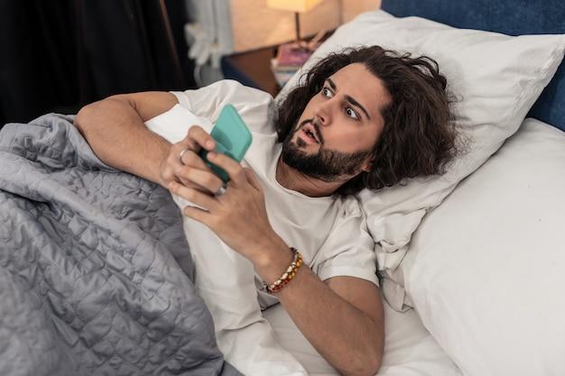 Zaspałem. emocjonalnie zestresowany mężczyzna patrzący na godzinę budząc się rano