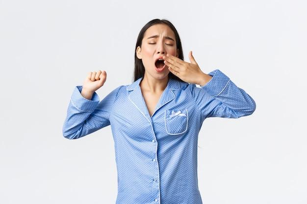 Zaspana azjatycka nastolatka w piżamie ziewa i przeciąga się, budząc się wcześnie z alarmu. zmęczona urocza kobieta w jammie stojąca na białym tle chce spać
