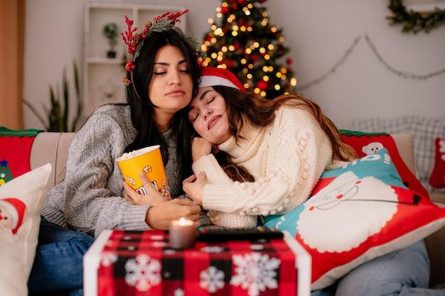 Zaspane ładne młode dziewczyny w czapce mikołaja i wieńcu ostrokrzewu trzymają wiaderko popcornu siedząc na fotelach i ciesząc się świętami w domu