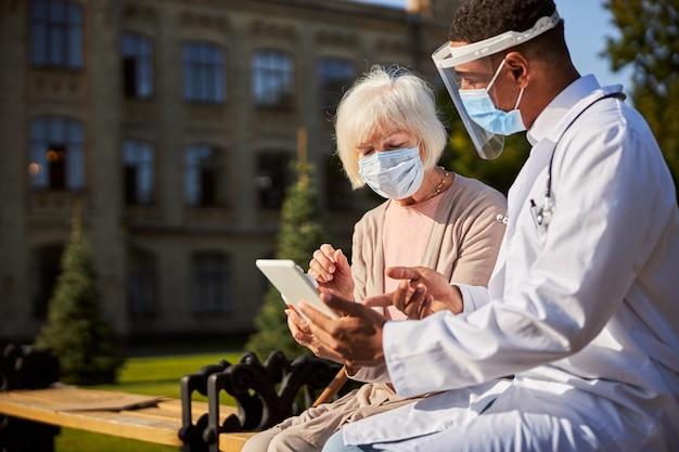 Zaspany emeryt siedzący i patrzący na tablet, słuchający wyjaśnień lekarza specjalisty