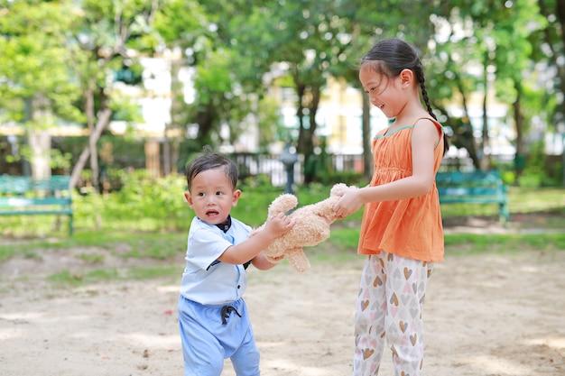 Zaspokoić małą azjatycką siostrę szurając lalką misia ze swoim młodszym bratem.