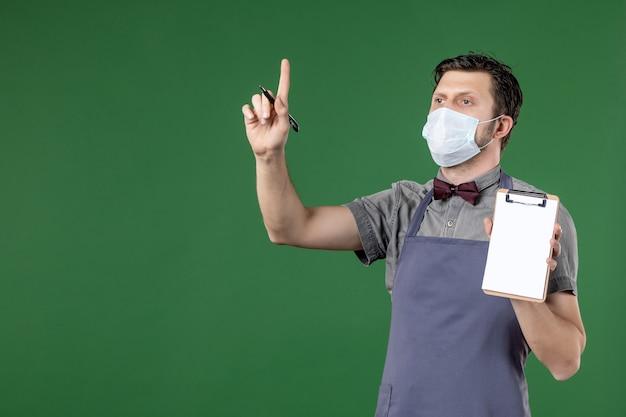 Zastanawiający się męski kelner w mundurze z maseczką medyczną i trzymający księgę zamówień piórem skierowanym w górę na zielonym tle