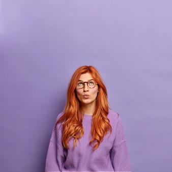 Zastanawiał się rudowłosa młoda kobieta trzyma złożone usta i patrzy w górę na miejsce