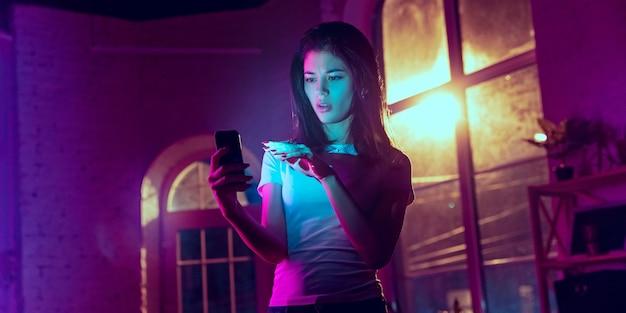 Zastanawiałem się. kinowy portret przystojnej stylowej kobiety w oświetlonym neonami wnętrzu. stonowane jak efekty kinowe w fioletowo-niebieskim kolorze. kaukaski modelki za pomocą smartfona w kolorowe światła w pomieszczeniu. ulotka.