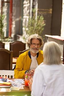 Zastanawiam się, gdzie iść. szczęśliwy mąż i żona siedząc w kawiarni przy ulicy i jedząc, planując poranny spacer.