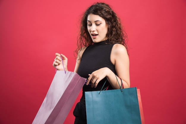 Zastanawiam się kobieta z trzema torbami na czerwonym tle. wysokiej jakości zdjęcie