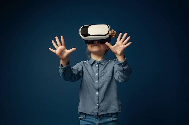 Zastanawianie się nad uczuciami. mała dziewczynka lub dziecko w dżinsach i koszuli z okularami zestawu słuchawkowego wirtualnej rzeczywistości na białym tle na niebieskim tle studio. koncepcja najnowocześniejszej technologii, gier wideo, innowacji.
