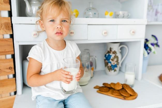 Zastanawiasz się dziewczyna trzyma szklankę mleka