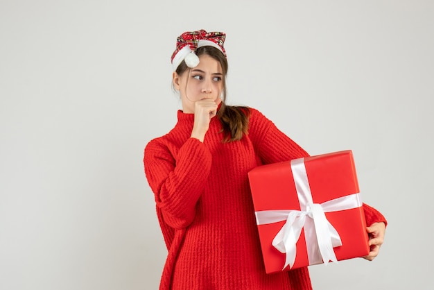 Zastanawiasz się dziewczyna z santa hat trzymając obecną stojącą na białym