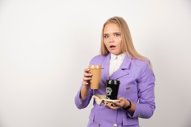 Zastanawiasz się, kobieta trzyma dwie filiżanki kawy na białym tle. wysokiej jakości zdjęcie