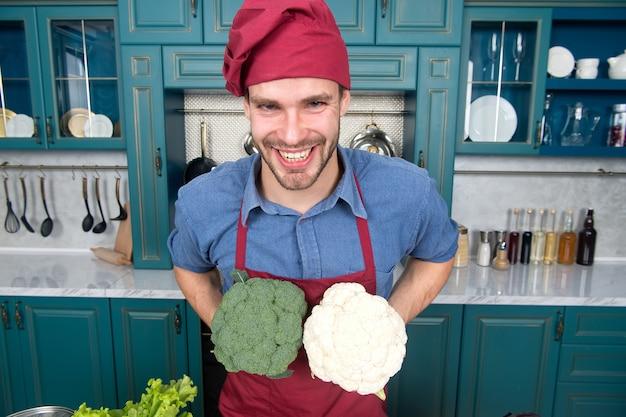 Zastąp ostrożnie. chociaż zamiany wydają się oczywiste, mogą być trudnym zadaniem. zrujnowane danie to strata czasu. mężczyzna szef kuchni zastępuje brokuły kalafiorem. uśmiechnięty szef kuchni zna kuchenne sztuczki.