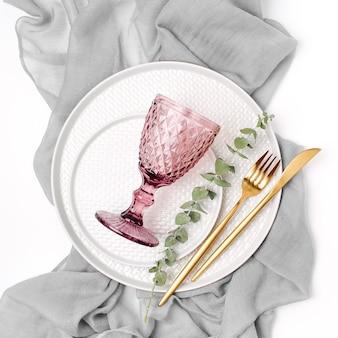 Zastawa stołowa i dekoracje do serwowania świątecznego stołu. talerze, kieliszki do wina i sztućce z szarej tkaniny dekoracyjnej na białym tle.