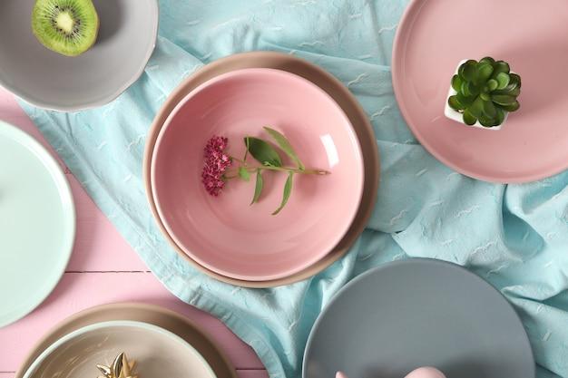 Zastawa stołowa i dekoracje na różowym drewnianym stole
