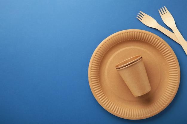 Zastawa stołowa z ekologicznego papieru rzemieślniczego. kubki papierowe, naczynia, torby, pojemniki fast food i drewniane sztućce na niebieskim tle. zero marnowania. koncepcja recyklingu. skopiuj miejsce