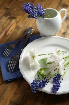 Zastawa stołowa z kwiatami na stole z bliska