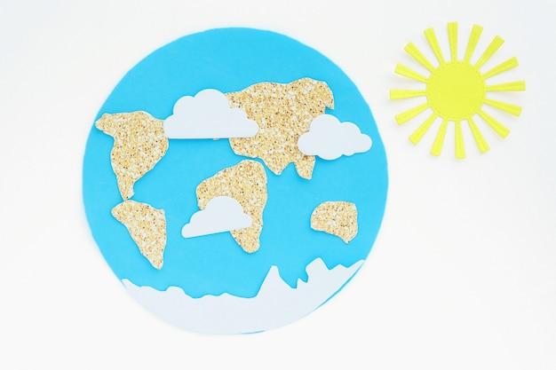 Zastosowanie papieru: planeta ziemia, kontynenty, chmury i słońce. izolować na białym tle.