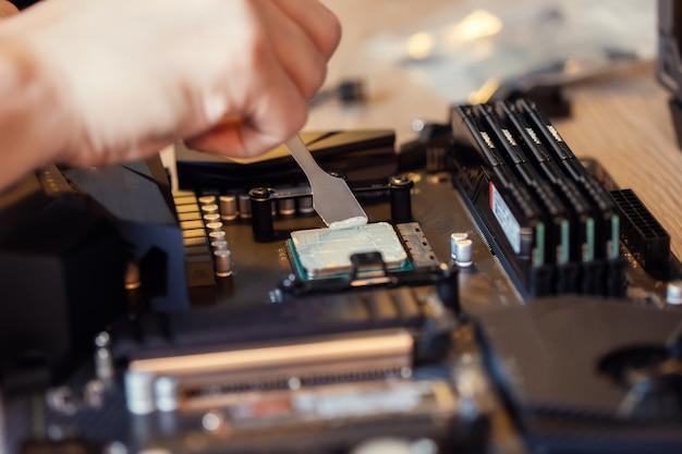 Zastosowanie pasty termicznej na chipie procesora komputera do wysokiej jakości chłodzenia. rozprowadzanie pasty termicznej za pomocą specjalnej szpatułki