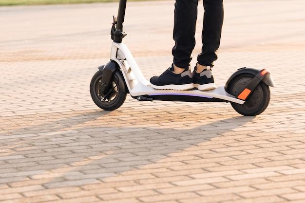 Zastrzelony na nogach młody człowiek w czarnych trampkach jeździ na elektrycznym skuterze o zachodzie słońca ecofriendly