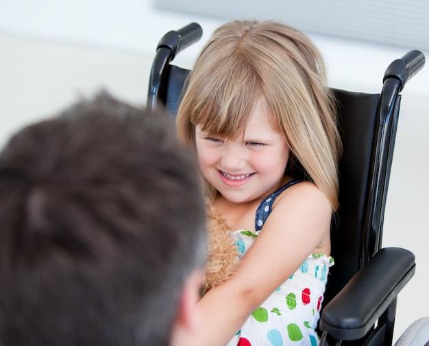 Zastrzeżona mała dziewczynka siedząca na wózku inwalidzkim