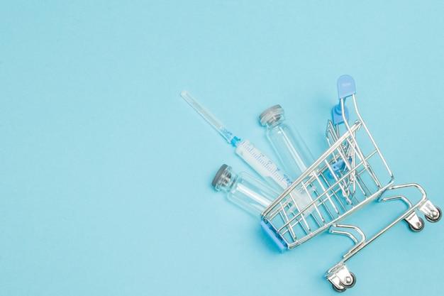 Zastrzyk medyczny w wózku sklepowym. kreatywny pomysł na koszt opieki zdrowotnej, aptekę, ubezpieczenie zdrowotne i koncepcję biznesową firmy farmaceutycznej. skopiuj miejsce