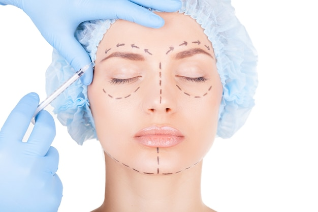 Zastrzyk z botoksu. atrakcyjna młoda kobieta w medycznym nakryciu głowy i szkicach na twarzy z zamkniętymi oczami, podczas gdy lekarze robią zastrzyk w twarz