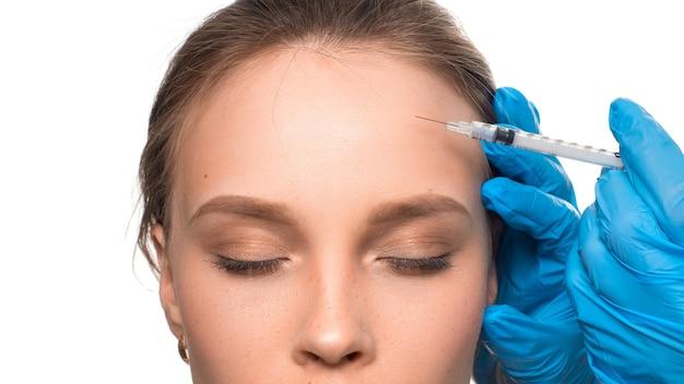 Zastrzyki kosmetyczne zbliżenie zobacz dłonie w rękawiczkach ze strzykawką wstrzyknij botox w obszar zmarszczek na t...