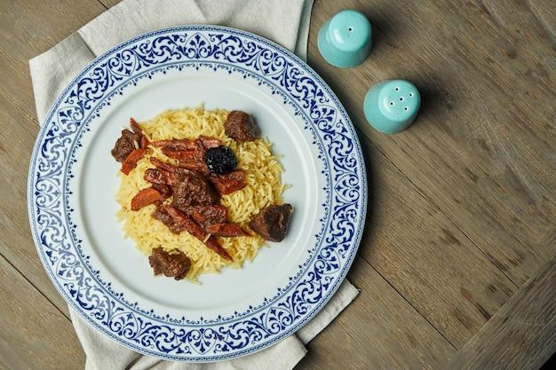 Zaświeca, dieta pilaw z wołowiną i marchewką na białym talerzu na drewnianej powierzchni. widok z góry z miejsca kopiowania tekstu. tradycyjna kuchnia orientalna
