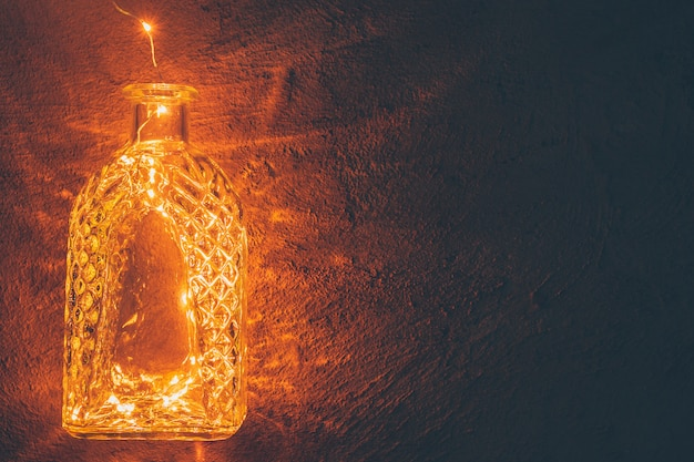 Zaświeca girlandę w szklanej butelce na ciemnym tle