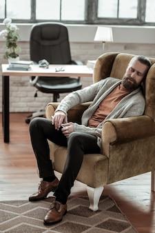 Zasypiam. brodaty doradca ubrany w szary sweterek zasypia w swoim fotelu w pracy