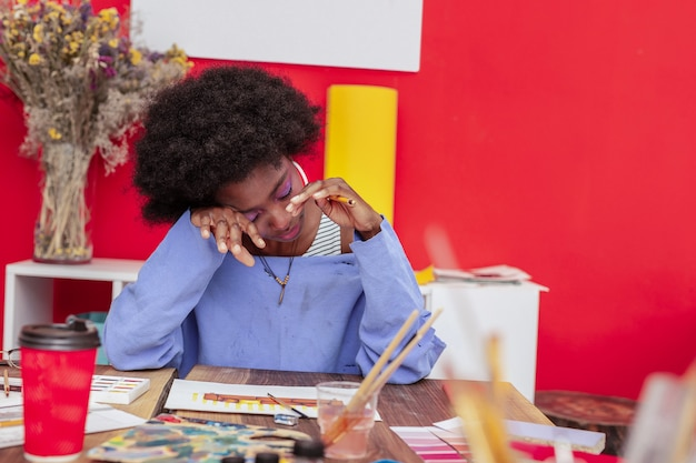 Zasypiam. zmęczony, wyczerpany projektant wnętrz w niebieskim swetrze zasypiającym w pracy