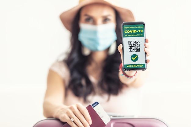 Zaszczepiona kobieta pokazuje swój cyfrowy zielony certyfikat na covid-19 w telefonie komórkowym z paszportem i biletem lotniczym, ma na twarzy maskę i jest gotowa do drogi.