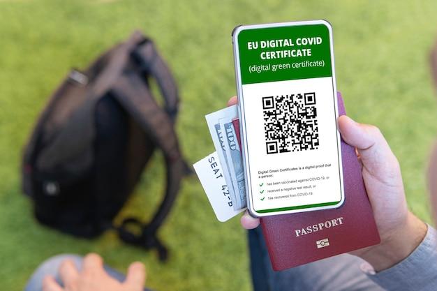 Zaszczepiona osoba korzystająca z aplikacji cyfrowego paszportu zdrowia w telefonie komórkowym do podróży podczas pandemii covid-19. zielony certyfikat. certyfikat potwierdzający szczepienie i obecność przeciwciał