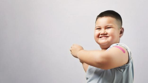 Zaszczepiony chłopiec pokazujący ramię po wstrzyknięciu szczepionki