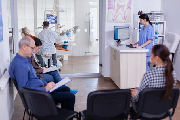 Zatłoczona poczekalnia stomatologiczna z osobami wypełniającymi formularze na konsultację stomatologiczną