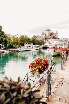 Zatoka kanału wodnego jeziora annecy z widokiem na czerwone kwiaty do przystani z miasta annecy. wysokiej jakości zdjęcie