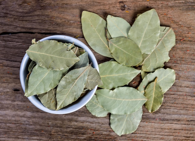 Zatoka liście w białym ceramicznym pucharze na drewnie