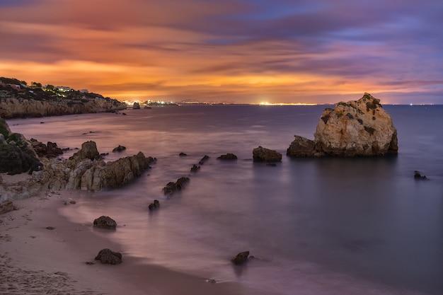 Zatoka morska w nocy albufeira. miasto w światłach.