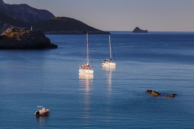 Zatoka morska z jachtami i łodzią w krystalicznie czystej lazurowej wodzie na wyspie paleokastritsa korfu grecja