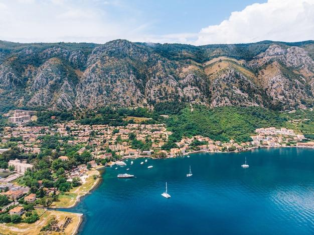 Zatoka morza śródziemnego z jachtami na tle wysokich gór w słoneczny dzień. widok z lotu ptaka. kotor, czarnogóra.