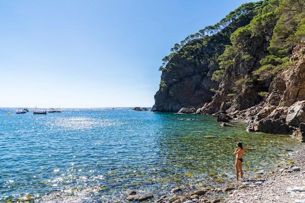 Zatoka pedrosa z kobietą nad brzegiem morza w llafranc w hiszpanii.
