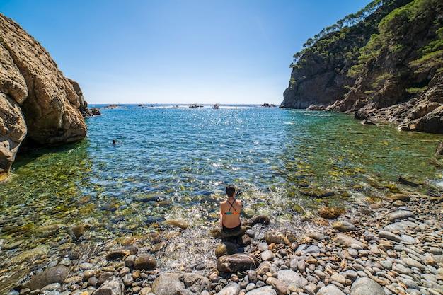 Zatoka pedrosa z kobietą siedzącą nad brzegiem morza w llafranc w hiszpanii.