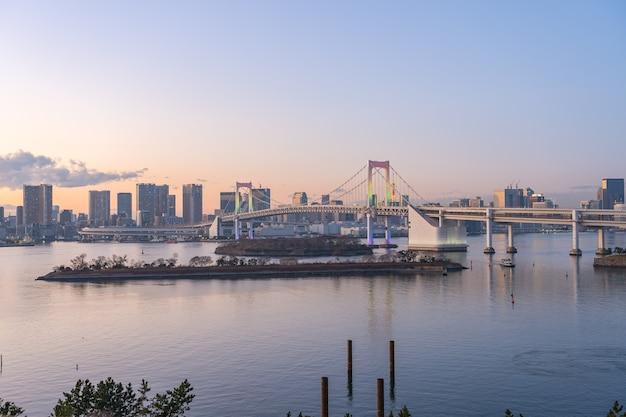 Zatoka tokio o zmierzchu z widokiem na rainbow bridge w mieście tokio, japonia.