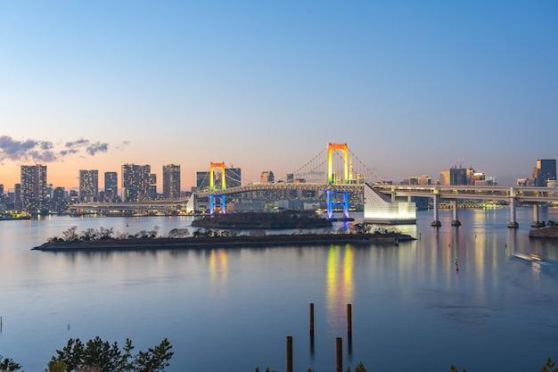 Zatoka tokio w nocy z widokiem na rainbow bridge w mieście tokio, japonia.