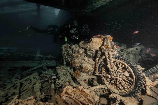 Zatopiony motocykl z ii wojny światowej na dnie morza. życie morskie pod wodą w błękitnym oceanie. obserwacja świata zwierząt. przygoda z nurkowaniem w morzu czerwonym, wybrzeże afryki