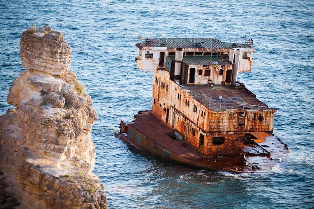 Zatopiony zardzewiały statek towarowy na wciąż błękitnych wodach morskich ze skałami dookoła