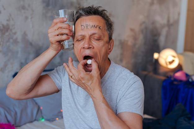 Zatrucie alkoholem. zmęczony dojrzały mężczyzna trzyma wodę i połyka pigułkę