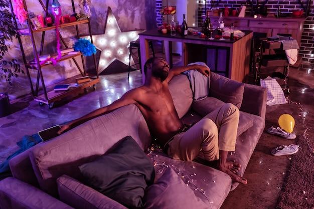 Zatrucie alkoholem. zmęczony i smutny człowiek przeżywający skutki szalonej zabawy we własnym domu