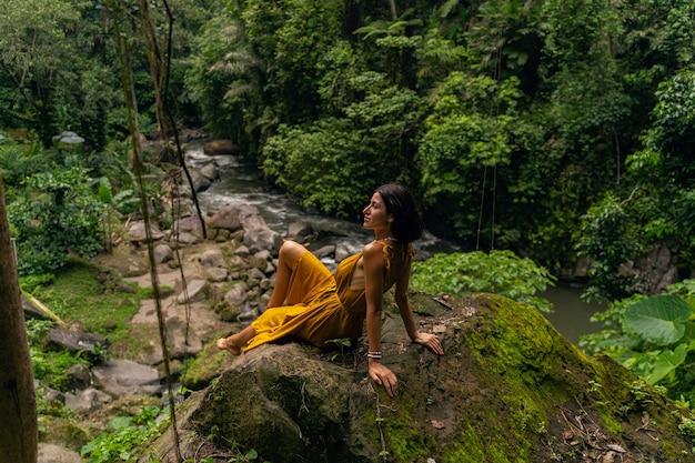 Zatrzymaj chwilę. ładna brunetka siedzi na kamieniu podczas przerwy podczas spaceru po lesie